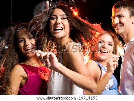 Portrait of laughing girl wearing white dress dancing among her friends - stock photo