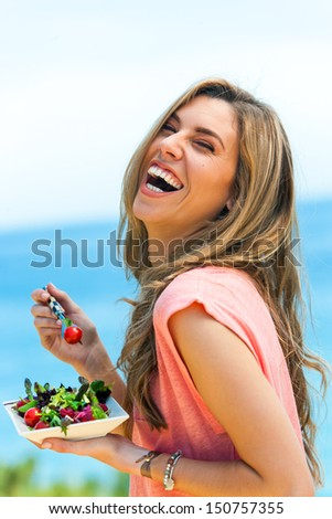 Portrait of laughing girl with green salad at seaside. - stock photo