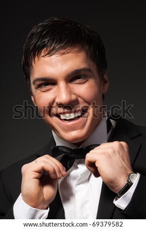 Portrait of laughing man in strict business suit set straight hits bow