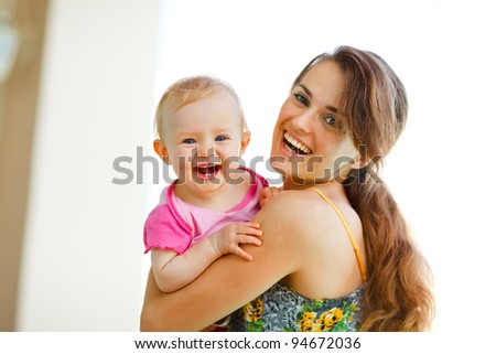 Portrait of laughing mother and baby - stock photo