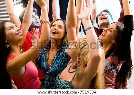 Portrait of laughing people raising their hands - stock photo