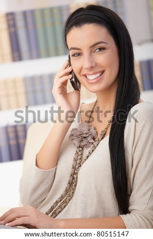 Portrait of laughing woman sitting on sofa with cellphone handheld, looking at camera.? - stock photo