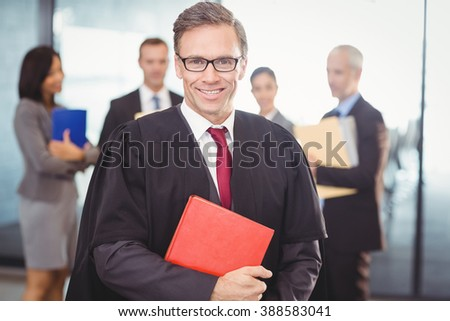 Portrait of lawyer holding a law book in office - stock photo