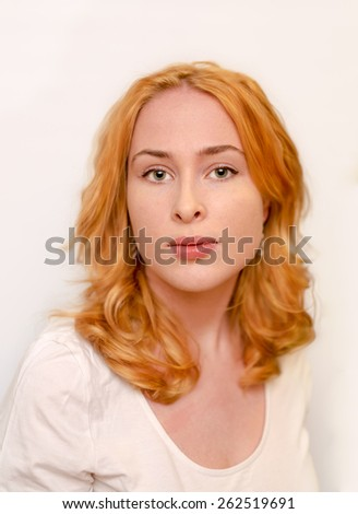 portrait of light red headed young caucasian woman looking at the camera - stock photo