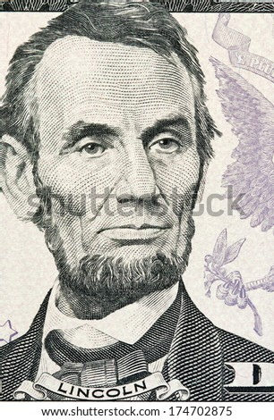 Portrait of Lincoln from five dollars bill new edition macro - stock photo