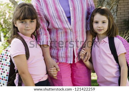 Portrait of little adorable daughters holding hands of mother - stock photo