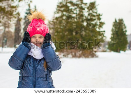 Portrait of little adorable girl in winter hat outdoors - stock photo