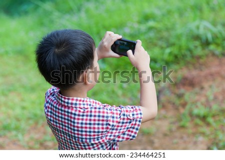 Portrait of little asian boy taking photos by digital camera on smartphone with good intentions, outdoor in the midst of glade on holiday - stock photo