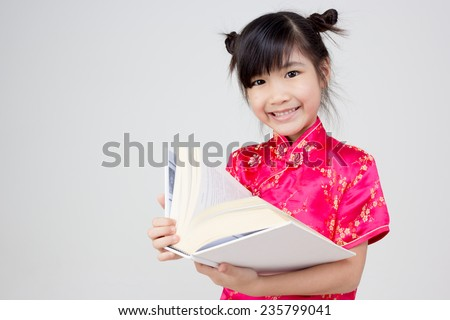 Portrait of little Asian child reading a book - stock photo