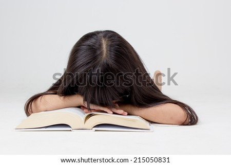 Portrait of little Asian child sleeping on a book  - stock photo