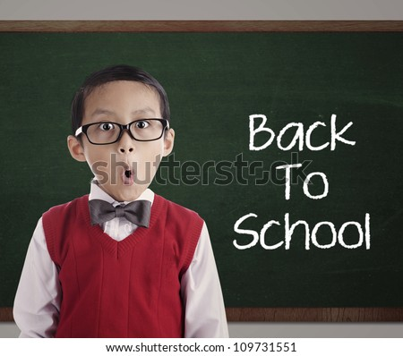 Portrait of little asian elementary school pupil with text of Back To School on the blackboard