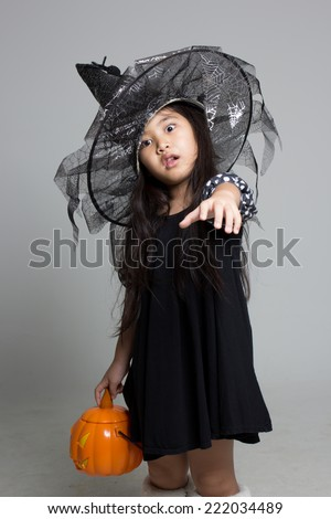 Portrait of little Asian girl in black hat and black clothing with pumpkin