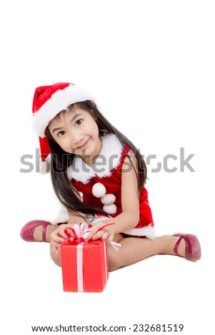 Portrait of little Asian girl in red Santa hat with gift box on white background