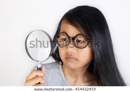 Portrait of little Asian student girl wearing glasses looking seriously trough magnifying glass