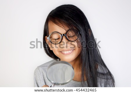 Portrait of little Asian student girl wearing glasses smiling when looking trough magnifying glass