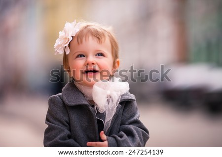 portrait of little baby girl in gray coat on the street in old city with funny smile. it is a one year old girl dressed on grey coat with big white flower in her hear and big white bow around her neck - stock photo