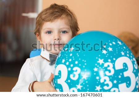 Portrait of little blond boy with baloon at his 3 birthday - stock photo