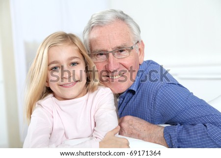 Portrait of little blond girl with grandfather - stock photo