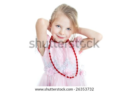 Portrait of little blonde girl putting on red beads