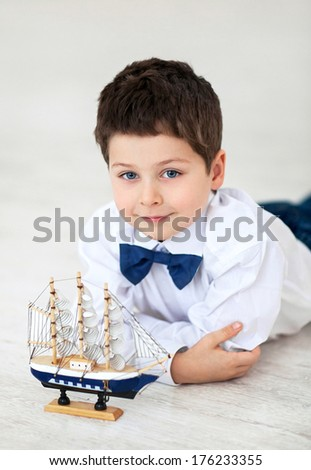 Portrait of little blue-eyed boy with the toy - stock photo