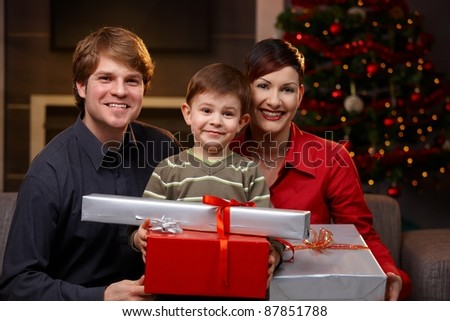 Portrait of little boy and happy parents holding christmas presents, smiling.? - stock photo