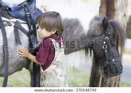Portrait of little boy and her horse - stock photo