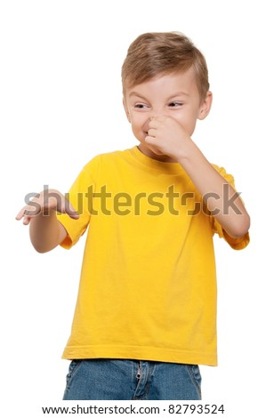 Portrait of little boy covering nose with hand on white background