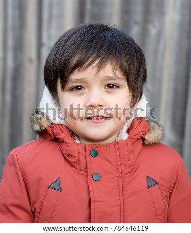 Portrait of little boy face get a small wound on his cheek by accident and looking at camera with smiling face, Toddler boy playing outside with warm clothes,Children Activities or Development Concept