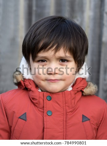 Portrait of little boy face get a small wound on his cheek by accident and looking at camera with funny face, Toddler boy playing outside with warm clothes,Children Activities or Development Concept
