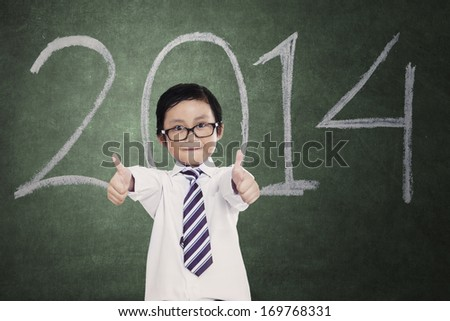 Portrait of little boy giving thumbs up in classroom - stock photo