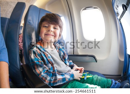 Portrait of little boy in airplane seat by window - stock photo