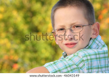 portrait of little boy in early fall park. he is looking at camera. - stock photo