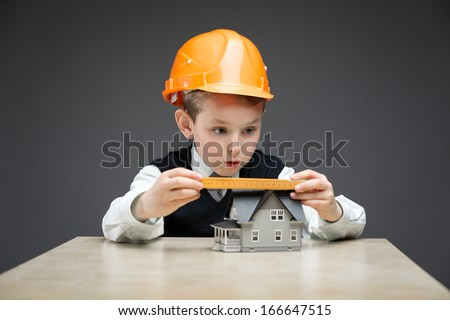 Portrait of little boy in headpiece with home model and ruler on grey background. Concept of real estate and engineering - stock photo