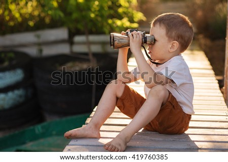 Portrait of little boy looking through binoculars on river bank. Barefoot child with binoculars sitting on the pier on river - stock photo