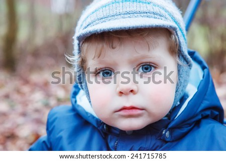 Portrait of little boy of one year in blue clothes outdoor. With big blue eyes, child looking at camera. - stock photo