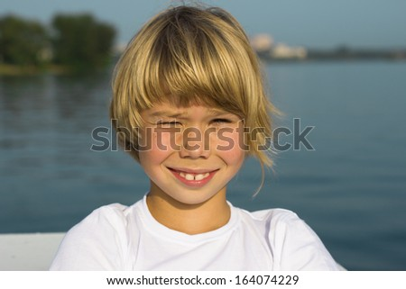 Portrait of little boy on a background summer landscape with water. - stock photo