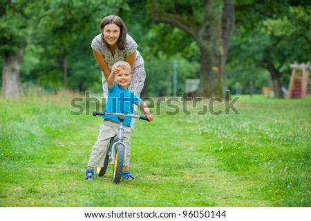 Portrait of little boy on a bicycle and his mother in the summer park - stock photo