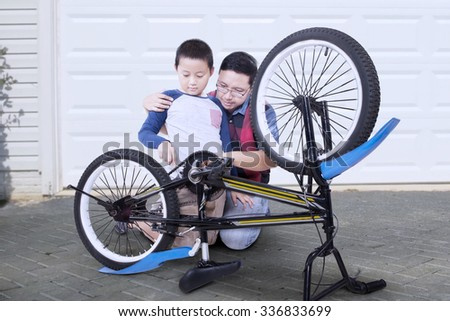 Portrait of little boy repairing bicycle gear with his dad helping him, shot at the garage - stock photo