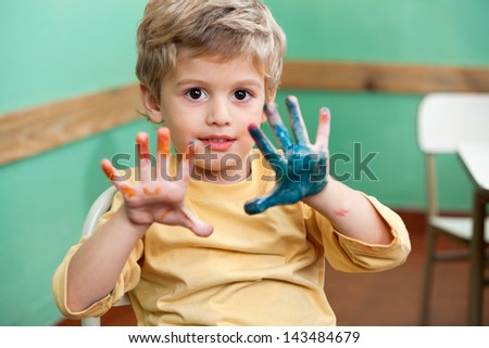 Portrait of little boy showing colored palms in art class - stock photo