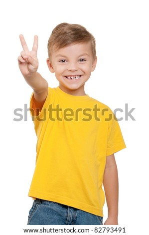 Portrait of little boy showing victory hand sign on white background