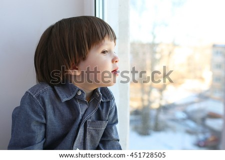 Portrait of little boy sits on sill and looks out of window in wintertime - stock photo