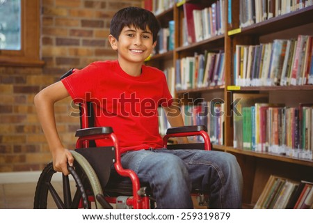 Portrait of little boy sitting in wheelchair at the library - stock photo