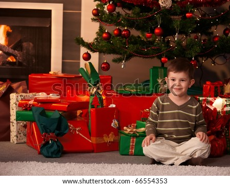Portrait of little boy sitting on floor in front of Christmas tree and presents, smiling.? - stock photo