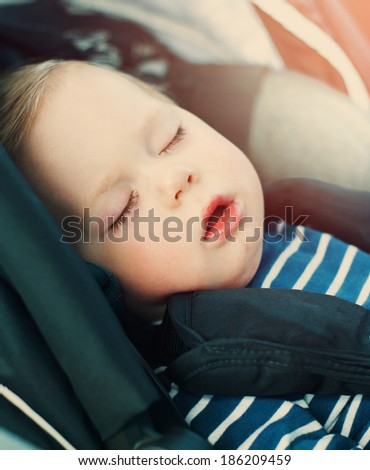 Portrait of Little Boy Sleeping in Car Seat, image with toning and effect of soft shining sun - stock photo