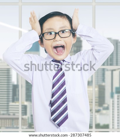 Portrait of little boy standing in the office and looks stressful near the window - stock photo