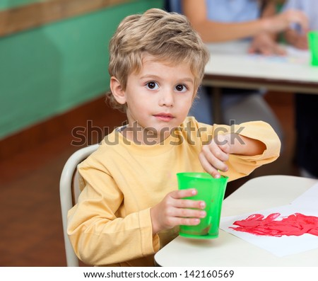 Portrait of little boy washing paintbrush in glass at classroom desk - stock photo