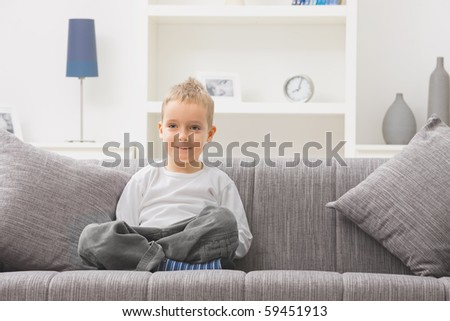 Portrait of little boy wearing white t-shirt, sitting at couch, looking at camera, smiling. - stock photo