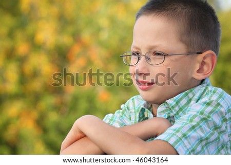 portrait of little boy with arms across in early fall park. he is looking away. - stock photo