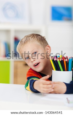 Portrait of little boy with colored pencils at table in house