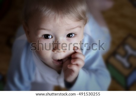 Portrait of little boy with finger in mouth